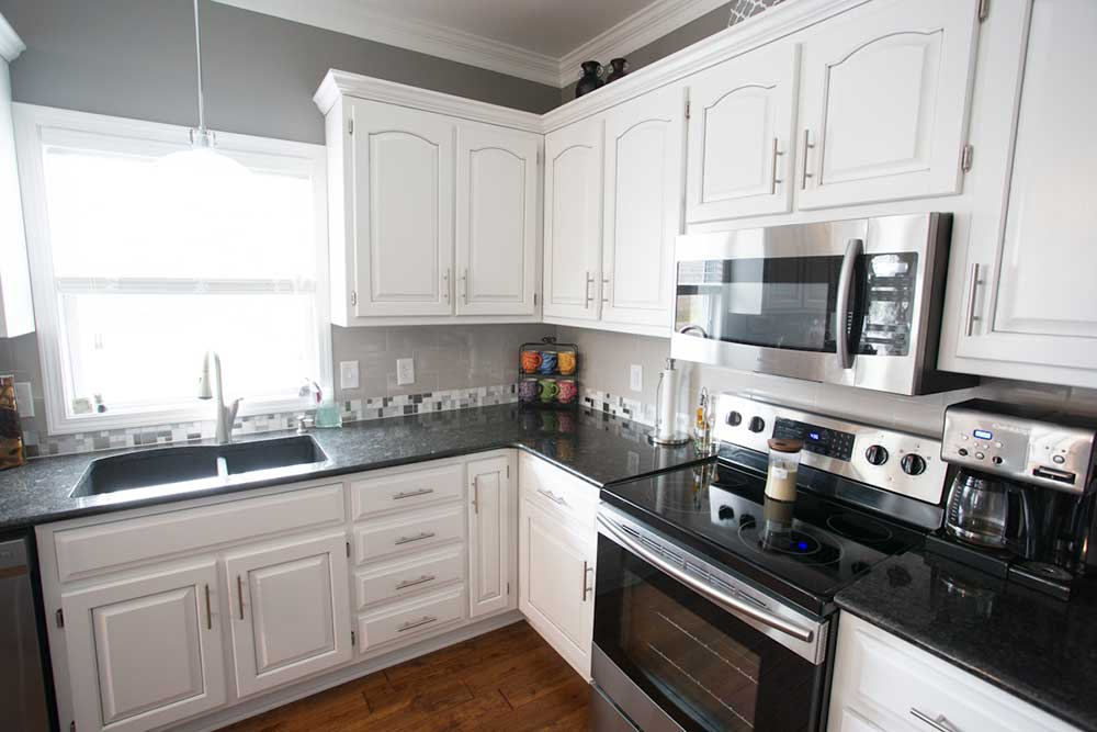 kitchen remodel-marble island countertop-white cabinets-pendant lights